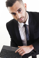 Portrait of young businessman with laptop isolated on white back