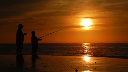 father teaching son how to fish in gorgeous sunset over ocean