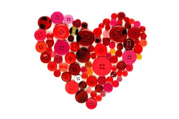 Heart shape of red and pink buttons over white