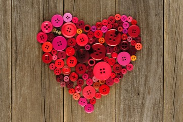 Heart shape of red and pink buttons over wood background