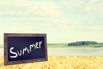 Summer concept with blackboard and calm landscape