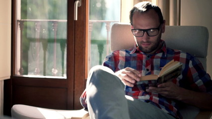 Handsome man reading book sitting on chair at home
