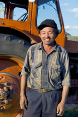 Smiling Mongolian Farmer Standing Next To The Tractor