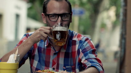 Portrait of happy man drinking beer sitting in cafe in city