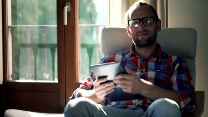 Portrait of happy man with tablet computer sitting on chair