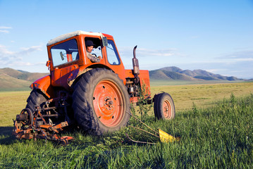 Mongolian Farmer Driving His Tractor On The Field