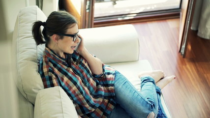 Young woman talking on cellphone sitting on sofa at home