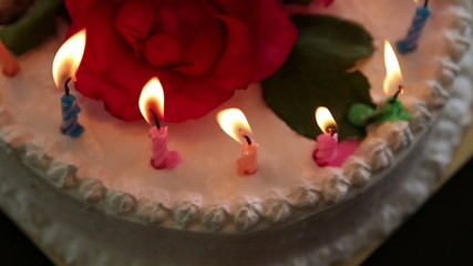 candle burning on a cream white cake with flowers