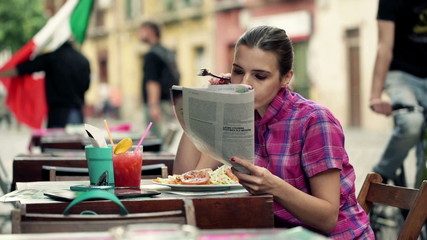 Beautiful woman reading magazine and eating salad in cafe