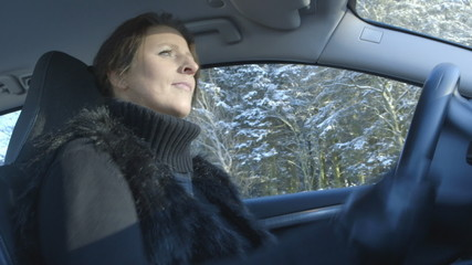 Woman driving a car on a beautiful winter day