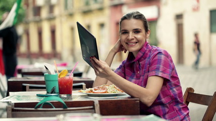 Portrait of happy, young woman with tablet computer in cafe