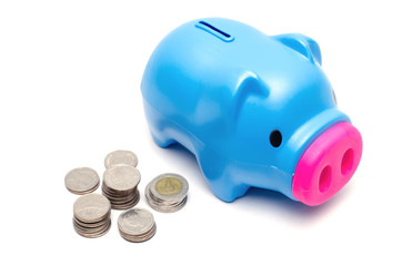Blue piggy bank or money box and coins on white background.