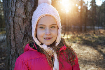 girl in winter cap and jacket outside on a sunny winter day