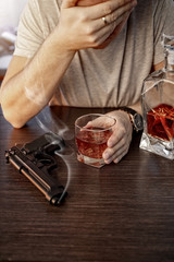 Devastated man with a gun and alcohol