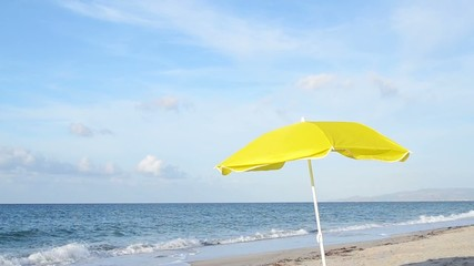 yellow parasol by the shore on a cloudy day