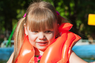 little girl in a life jacket smiling