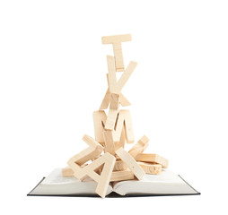 Pile of wooden letters over the book