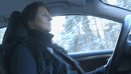 Woman is driving a car on a beautiful winter day