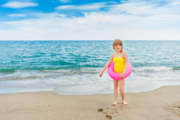 Adorable little girl with pink inflatable ring by the sea