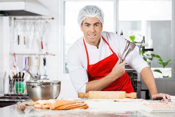 Confident Chef Holding Tongs While Preparing Ravioli Pasta In Ki