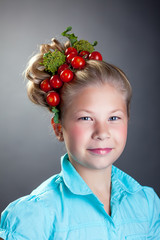 Lovely little girl posing with wreath of tomatoes