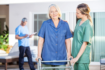 Nurse Assisting Senior Woman To Walk With Zimmer Frame