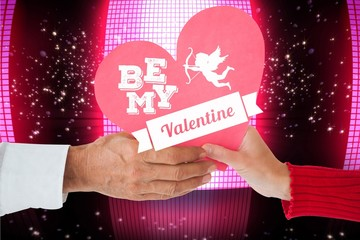 Composite image of couple holding heart