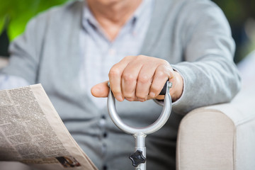 Midsection Of Senior Man With Newspaper And Cane