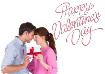 Composite image of loving couple holding a gift