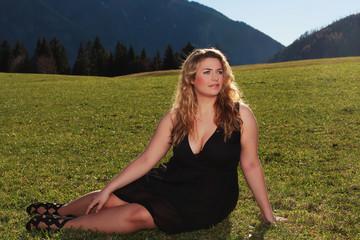 Frau mit Übergröße halb liegend auf einer Wiese in den Alpen