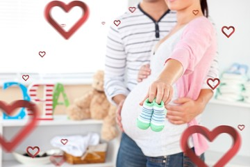 Bright pregnant woman holding baby shoes