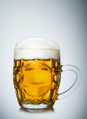 Mug full of fresh beer isolated on white