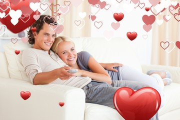 Composite image of couple cuddling while watching tv