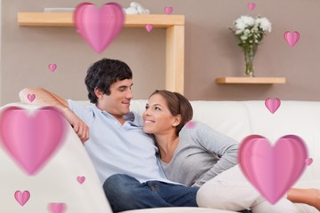 Composite image of couple on the sofa in love