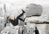 Fototapety Young businessman scaling a rock