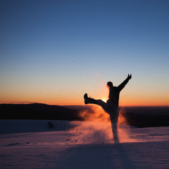 silhouetted man kicking snow in winter landscape