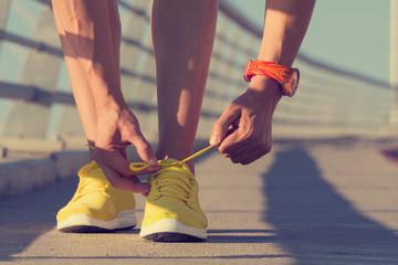 Jogger tying his shoes on a big bridge.