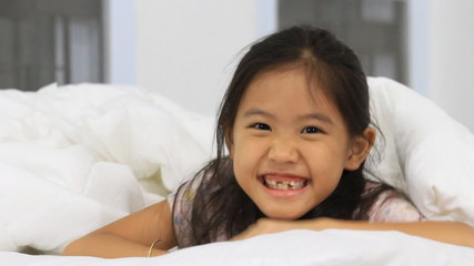 Little Asian girl play hide and seek on the bed
