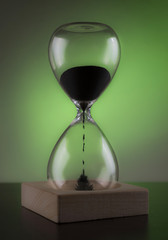 Hourglass on the table. Green background.