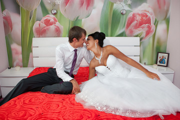 groom and  bride in a bedroom on a white bed