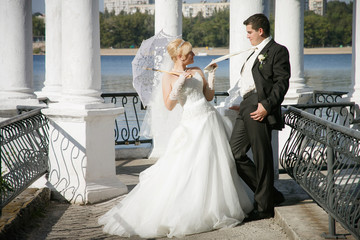 bride with a white umbrella and  groom stand near the river