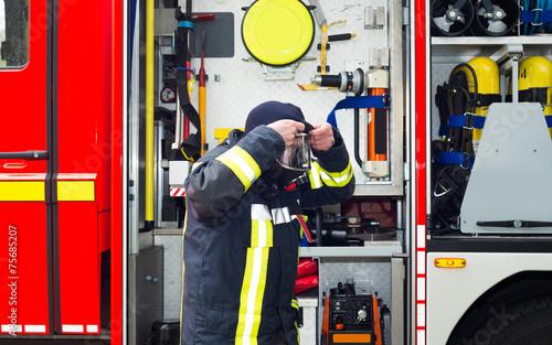 Leinwanddruck Bild Feuerwehrmann im Einsatz mit Atemschutzmaske