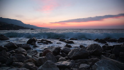 Waves break about stones at sunrise over the sea