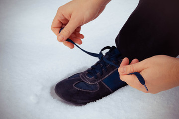 man tying shoelaces in sneakers on the background of snow