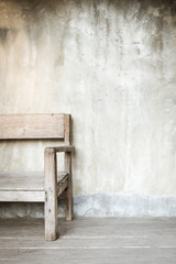 Old chair in front of concrete wall with copy space