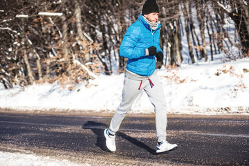 Young athlete going for a run outdoor in snow