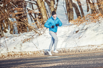Muscular athlete working out outdoor on a cold winter day