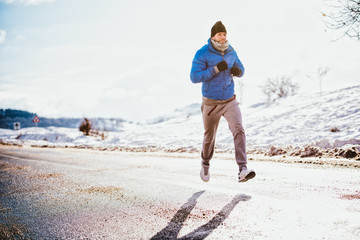 close-up of man running and jogging on a cold winter day