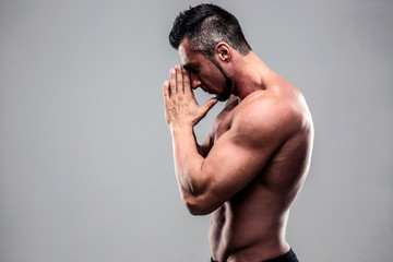 Portrait of a young muscular man praying over gray background