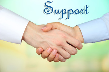 Business handshake symbolizing support on color background